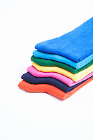 Colorful stack of folded socks over white background
