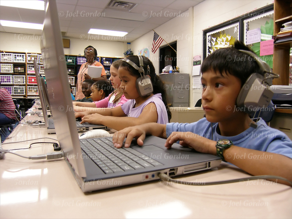 Elementary 3rd grade students wearing headphones and using laptop computers practicing reading sitting at their tables in Computer Reading Lab in Middleton-Burney Elementary Crescent City FL