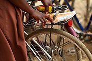 A girl takes her school books of the back of her bicycle, Ghana.