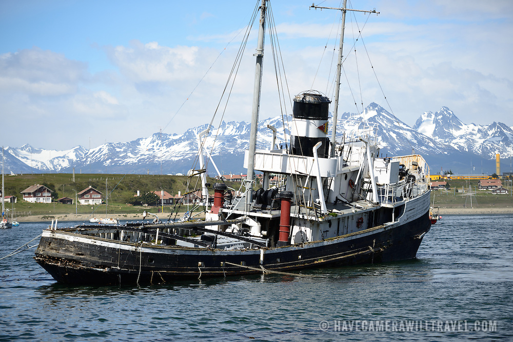 The wreck of the Saint Christopher (HMS Justice) aground in the harbor of Ushuaia, Argentina. The Sain Christopher is an American-built rescue tug that served in the British Royal Navy in World War II. After the war she was decommissioned from the Royal Nay and sold for salvage operations in the Beagle Channel. After suffering engine problems in 1954, she was beached in 1957 in Ushuaia's harbor where she now serves as monument to the shipwrecks of the region. The snow-capped mountains in the distance are across the Beagle Channel in Chile.