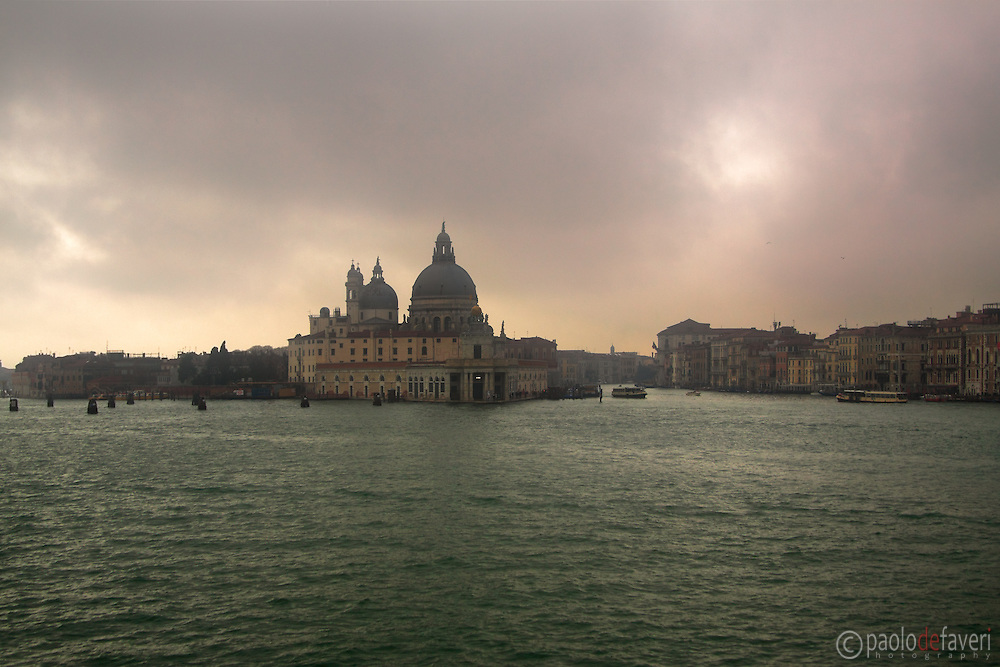 Thick layers of fog raising above the lagoon and the San Marco basin, with the church of La Salute and Punta della Dogana in the bacground.