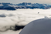 Legendary Finnish snowboarder Jussi Oksanen flies above the clouds over the Whistler Valley in the Brandywine backcountry in Southwestern British Columbia