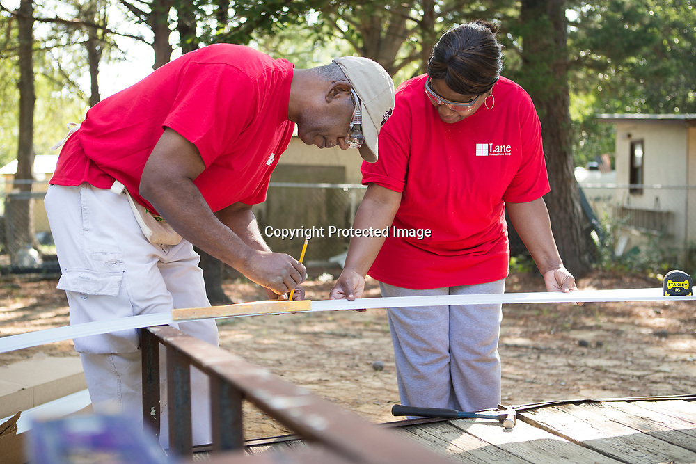 Myron and Brenda Penro measure siding as they and other Lane Furniture employees volunteer their time building a Habitat for Humanity home Friday morning in Verona.