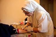 Roma 19 Novembre 2011.Servizio di assistenza domiciliare per malati di A.I.D.S.La suora che si occupa dell'assistenza domiciliare si prepara  per il prelievo del sangue ad un malato di A.I.D.S...