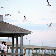 A couple watches seagulls flock for food at Wrightsville Beach, NC at sunset.