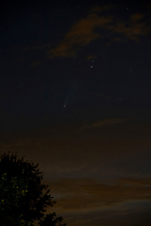 Comet Neowise makes an appearance in the northwest skies about halfway between the horizon and the bottom of the Big Dipper constellation.  Clouds and other stars dot the otherwise clear sky.