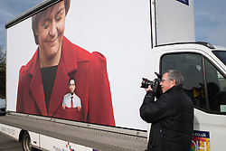 © Licensed to London News Pictures . 13/04/2015 . Manchester , UK . A photographer photographing a Conservative Party stunt opposite Old Granada Studios featuring ad vans with Ed Miliband depicted in the pockets of the SNP ahead of Ed Miliband launching the Labour Party manifesto ahead of the General Election at the Old Granada Studios in Manchester , UK . Photo credit : Joel Goodman/LNP