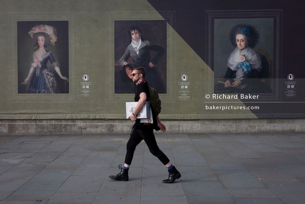 A male hipster wasks past Goya portraits, sponsored by Credit Suisse and advertised on a construction hoarding outside the National Portrait Gallery.