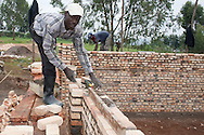 Photo Randy Vanderveen.Nyrusange, Rwanda.A brick layer works on the wall of a new school class room under construction at the Gary Scheer school in rural south Rwanda. Classrooms at schools in the nation have to be all be built of fired-brick as part of the country's Vision 2020 mandate.