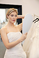 Beautiful young woman dressed up in wedding gown looking in hand mirror