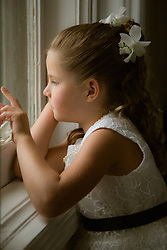 little girl in a formal dress with finger up to a window