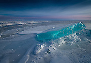 """Incredible Turquoise Ice Gleams Like Gemstones On Lake Baikal<br /> <br /> Landscape photographer Alexey Trofimov, who lives in Siberia, took these incredible pictures of the unusual phenomenon. Trofimov describes Lake Baikal itself as """"the pearl of our planet."""" Perhaps, then, the extraordinary blue-colored ice formations are its accompanying sapphires.<br /> Lake Baikal is indeed remarkable, even without these striking icy marvels. Located in southeastern Siberia, the over 7.78 million-acre expanse of water is notable for being Earth's most ancient lake, dating back as it does some 25 million years. The bottom of this gigantic basin, meanwhile, lies 3,892 feet below sea level. However, the distance from the water's surface to its nethermost-recorded point measures an amazing 5,387 feet. Baikal is, in short, the deepest lake on the planet.<br /> <br /> Moreover, the lake's surroundings are exceptionally varied. Near to the huge body of water """"there are,"""" as Trofimov tells us, """"high mountain ranges, impassable taiga, sandy beaches [and] wild steppes."""" The weather is also fickle, with Baikal often bathed in sunshine but adjacent landforms or even other parts of the lake prone to experiencing very different conditions such as storms. Trofimov suggests that this contributes to the place being """"harsh and dangerous as [well as] beautiful.""""<br /> <br /> Given the intriguing array of environmental spectacles in, over and around the lake, it seems a fitting place to find a captivating wonder like the turquoise ice formations pictured here. The brightly hued ice reveals itself around March each year, and many people make their way to the area in order to witness its beauty at this time.<br /> <br /> These unique frozen formations are in fact called ice hummocks. Theknolls are created in part by pressure that develops gradually and unevenly in the layer of ice that covers Lake Baikal in winter. The physical make-up and temperature of the ice sheet then also become imbalanced, """