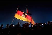 03 Oct 1990, near the Reichstag, Berlin, Germany --- Standing in a crowd of revelers, people wave German flags during festivities celebrating the reunification of East and West Germany into the single country of Germany. October 3, 1990. --- Image by © Owen Franken/CORBIS
