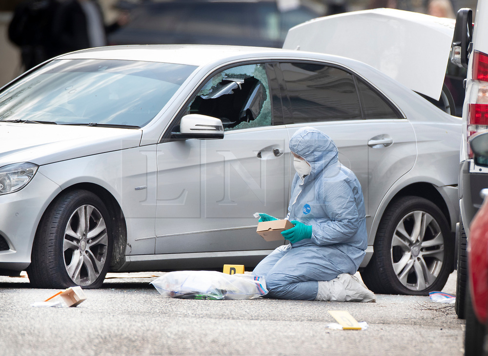 © Licensed to London News Pictures. 13/04/2019. London, UK. A police forensics officer puts evidence in a box next to car with a smashed window and deflated tyres in Holland Park after shots were fired by police near the Ukrainian embassy. Photo credit: Peter Macdiarmid/LNP