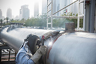 Manual worker welding a large gas pipe. Oil and gas industry arc welder  with protective visor to protect him from bright light and sparks.