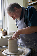 A potter working with clay at his wheel in Pinmore ceramics gallery, Girvan, Ayrshire.