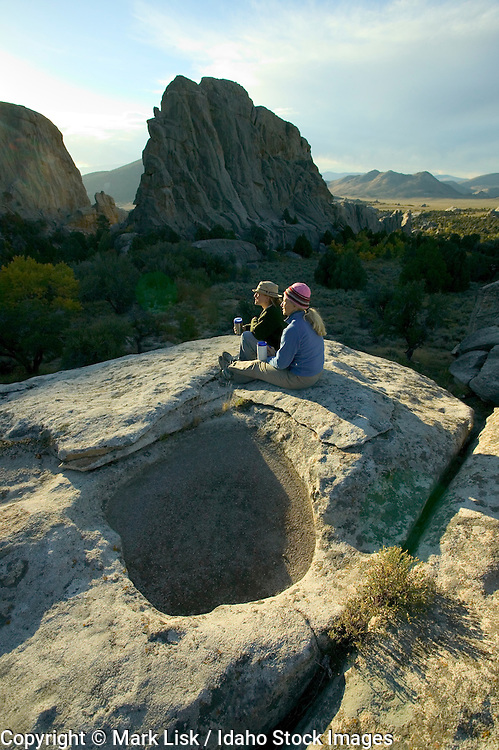 (MR) hikers relaxing on a rock at the City of Rocks, Idaho.