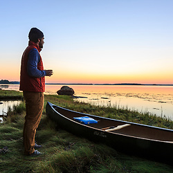 A man drinks a cup of coffee at sunrise on Lanes Island in Casco Bay. Yarmouth, Maine.