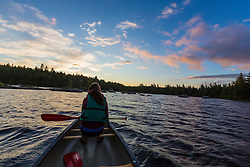 A teenage girl paddles in the bow of a canoe on Bald Mountain Pond. Bald Mountain Township, Maine.
