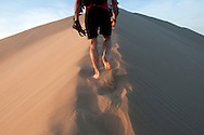 Luca Sommaruga Malaguti climbs the dunes outside of Huacachina, Peru, at sunset.