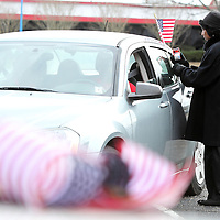 Adam Robison | BUY AT PHOTOS.DJOURNAL.COM<br /> Vonnia Gray Clay, of Tupelo, tapes an American flag on the back window of a car that is in line for the MLK Motorcade that starts at the VF Outlet and travels to St. Paul United Methodist Church. The motorcade is sopnsored by the Modern Beautician Club of Tupelo.