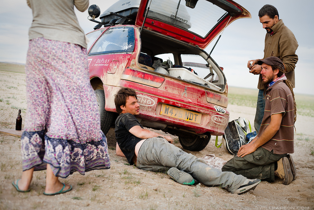 Alec, an architect from England, pauses after realizing that a combination of bubble gum, silicone and liquid metal failed to patch a large oil leak west of Bayan-Khongor, Mongolia. He and his girlfriend received a tow to Ulaanbaatar, but were still able to donate the car.