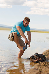 man removing his sock while falling over in a lake
