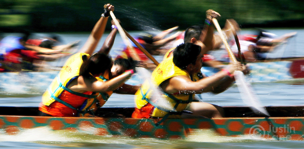 Competitors paddle toward the finish line during the annual Hong Kong Dragon Boat Festival in Queens, New York on Sunday, 13 August 2006.