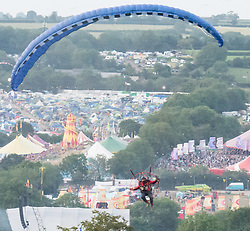 © Licensed to London News Pictures. 27/06/2015. Pilton, UK.  A man jumps the Glastonbury Festival wall without a ticket by flying into the festival in a light propellor-driven motorised aircraft, landing in next to the Stone Circle at 9pm to cheers from the watching festival goers.  Festival officials were quick on scene confiscating the aircraft but allowing the man to walk free.  Asked for a quote by the photographer the man said 'I need a beer'.  This years headline acts include Kanye West, who is due onstage later his evening, The Who and Florence and the Machine, the latter being upgraded in the bill to replace original headline act Foo Fighters. Photo credit: Richard Isaac/LNP