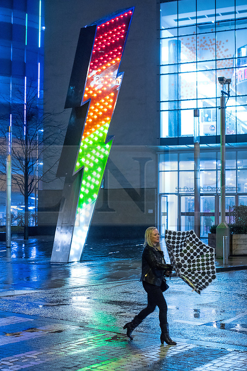 © Licensed to London News Pictures . 18/03/2017 . Cardiff , UK. A woman holds on to an inverted umbrella in a strong gust of wind . Revellers on a windy and wet Saint Patrick's Day night out in Cardiff city Centre . Photo credit: Joel Goodman/LNP