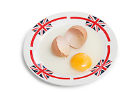 Broken brown egg on plate over white background