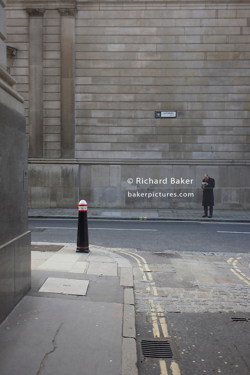 A lone traffic bollard and one solitary pedestrian on the corner of Lothbury and Tokenhouse Yard, two narrow and historic streets with the high walls of the Bank of England in the background -  in the City of London, the capital's financial district. The area was populated with coppersmiths in the Middle Ages before later becoming home to a number of merchants and bankers. Lothbury borders the Bank of England on the building's northern side. Tokenhouse St dates from Charles I and was where farthing tokens were coined. The City of London is the capital's historic centre first occupied by the Romans then expanded during following centuries until today, it has a resident population of under 10,000 but a daily working population of 311,000.