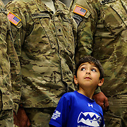 Kris Wilson/News Tribune.Santiago Calle looks up at the soldiers around him as he stands in formation with his dad, Specialist Juan Calle during the invocation and opening remarks as the Missouri National Guard 548th Transportation Company celebrated their homecoming at the Ike Skelton Training Site on Saturday following a year-long tour in Afghanistan.