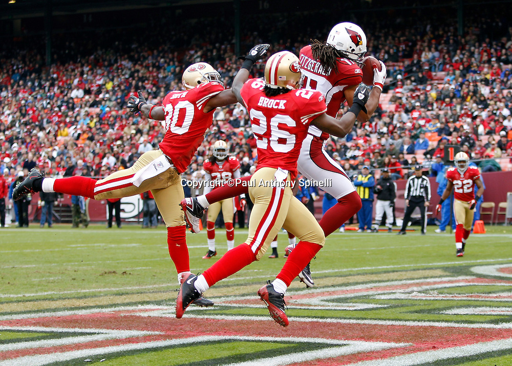 Arizona Cardinals wide receiver Larry Fitzgerald (11) leaps and catches a second quarter touchdown pass that cuts the San Francisco 49ers lead to 10-7 while covered by San Francisco 49ers safety Reggie Smith (30) and San Francisco 49ers cornerback Tramaine Brock (26) during the NFL week 17 football game on Sunday, January 2, 2011 in San Francisco, California. The 49ers won the game 38-7. (©Paul Anthony Spinelli)