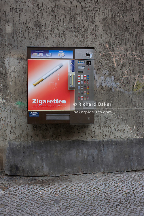 A cigarette dispenser mounted to an apartment block wall in Wedding, a north-western district of Berlin.