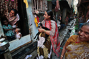 Women get together in the narrow alley ways between the homes.  The slum of Cheetah Camp on the outskirts of Mumbai, India is a predominantly muslim community on living on the fringe while the city continues to grow.