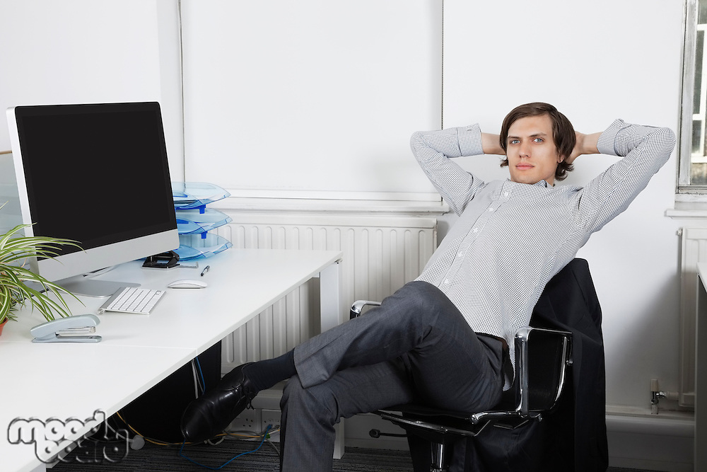 Portrait of young businessman relaxing on chair with hands behind head in office