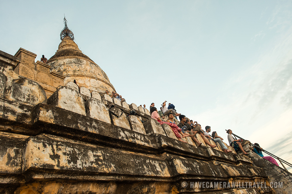 BAGAN, Myanmar (Burma) - Tourists watching the sunrise from the top of one of the handful of pagodas in Bagan that are open for climbing. Bagan was the ancient capital of the Kingdom of Pagan. During its height, from the 9th to the 13th century, over 10,000 Buddhist temples and pagodas were built. Several thousand of them survive today.