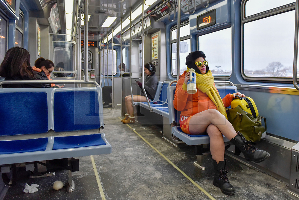 "© Licensed to London News Pictures. 07/01/2018. CHICAGO, USA.  Participants take part in the annual ""No Pants Subway Ride"", a fun event taking place both in Chicago and worldwide, where people ride the subway wearing no trousers.  With Chicago experiencing an extreme cold snap currently, temperatures made taking part more challenging.  Photo credit: Stephen Chung/LNP"