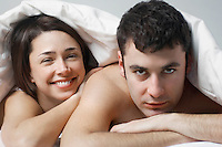 Couple lying in bed portrait close up