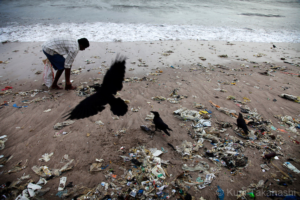 A scavenger picks up recyclable and salable garbage on the beach in Mumbai, India. The economical capital city is facing serious environmental issues as its population grows rapidly.