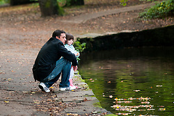 Man and child Watching the Ducks on the pond in Endcliffe Park Sheffield<br />