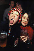 Two drunk asian women drinking pints of beer, London, U.K, 2000.