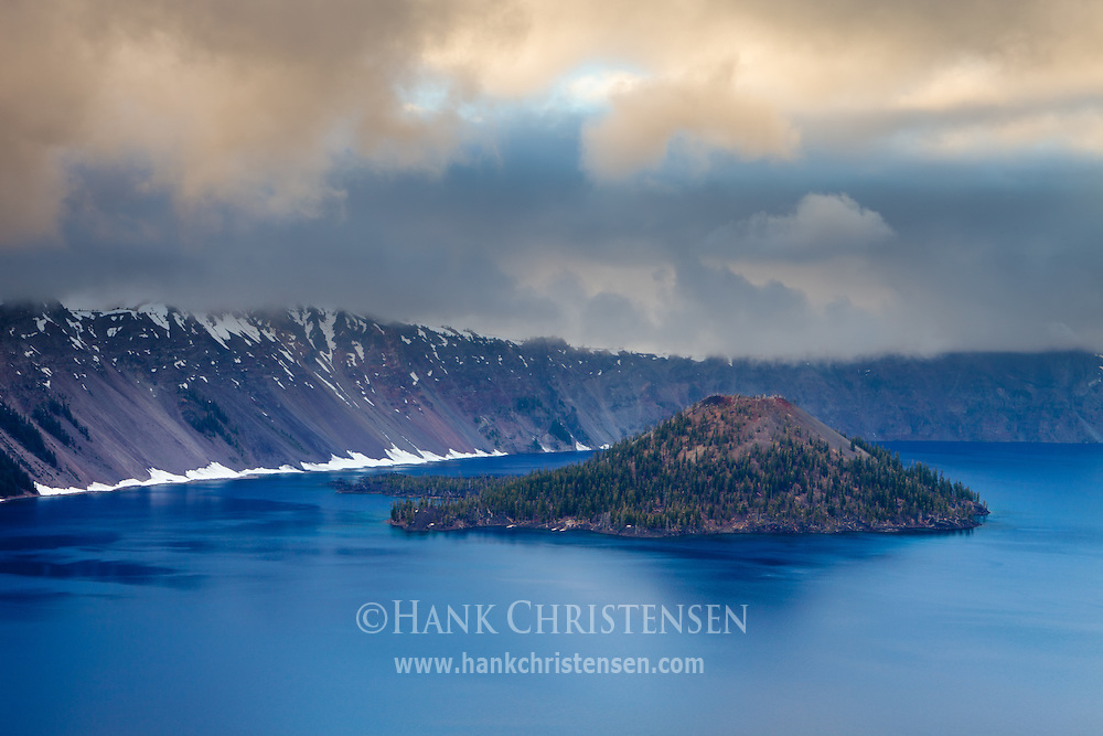 The orange hues of sunset light the overcast sky over Wizard Island, Crater Lake National Park, Oregon
