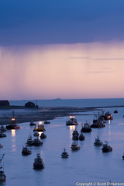 Commercial salmon fishing boats rest at anchor in the Naknek River after sunset while rain falls in the distance, Bristol Bay, Alaska.
