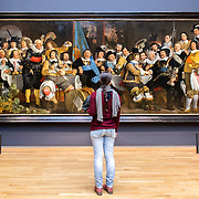 AMSTERDAM, NETHERLANDS - FEBRUARY 08: Visitor at Rijksmuseum admiring Banquet at the Crossbowmen's Guild in Celebration of the Treaty of Münster, by Bartholomeus van der Helst, on February 08, 2015 in Amsterdam. The Rijksmuseum is located at the Museum Square, and first opened its doors in 1885.