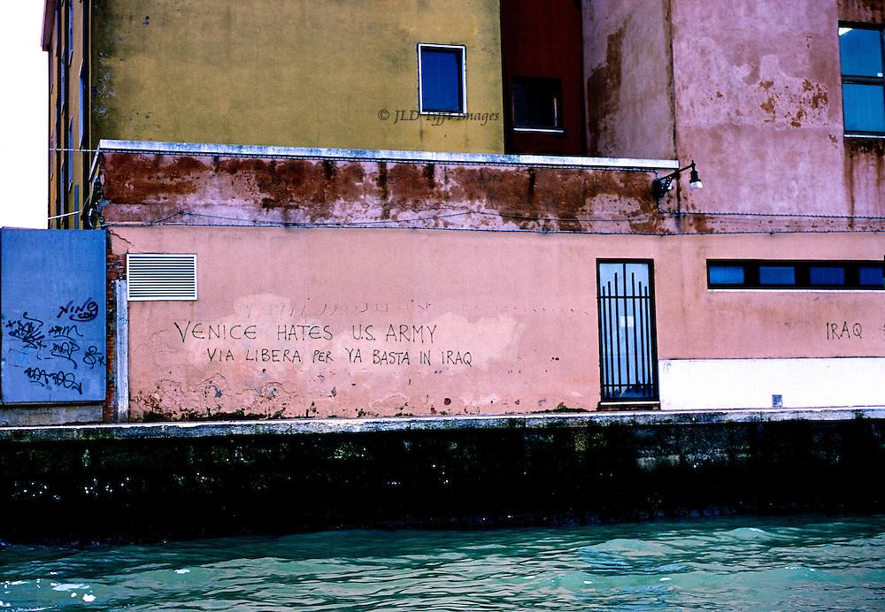 """Graffiti on a pink wall by a Venetian canal: """"VENICE HATES US. ARMY VIA LIBERA PER YA BASTA IN IRAQ"""""""