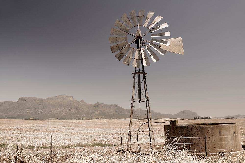 Wind wheel in fields with Mountain Range in the back near Piketberg, Western Cape, South Africa