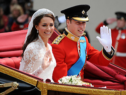 Prince William of Wales and his bride Catherine Middleton drive down the Mall in an open carriage on their way into Buckingham Palace following their wedding at Westminster Abbey on Friday 29 April 2011. in London, England.