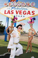 Female dancers and Elvis impersonator posing in front of Las Vegas welcome sign, Nevada, USA